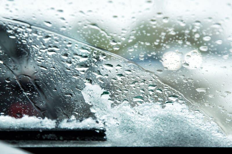 Schneebedeckte Autowindschutzscheibe mit geschmolzenen Schneetropfen und -Scheibenwischern Unscharfe Lichter des Führens von Auto stockbild