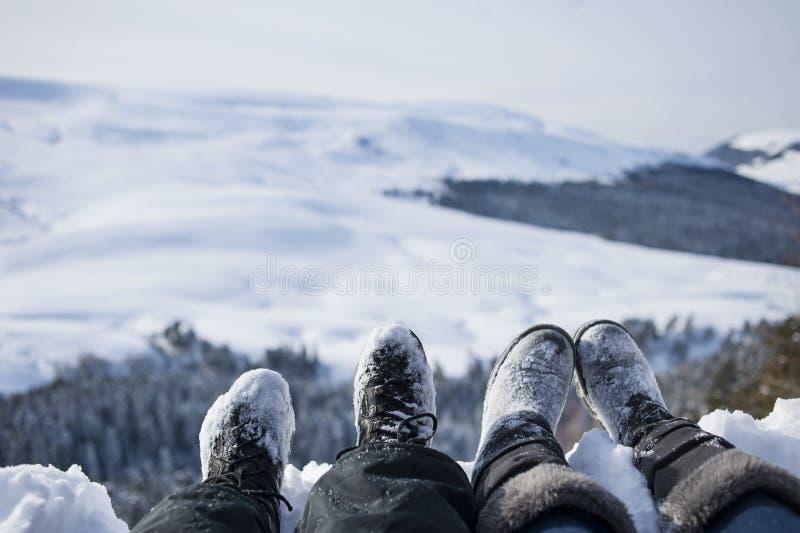 Schneebedeckte Füße von zwei Wanderern auf einem Winter gestalten landschaftlich stockfotografie