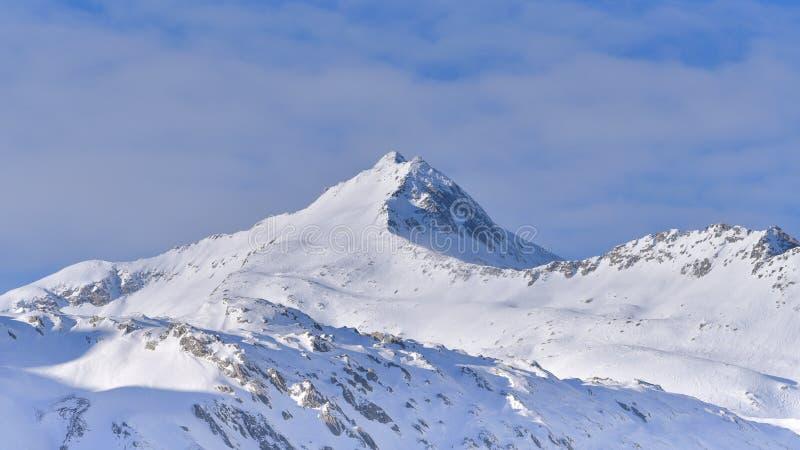 Schneebedeckte Gebirgsspitze, mit Wolken hinten lizenzfreies stockbild