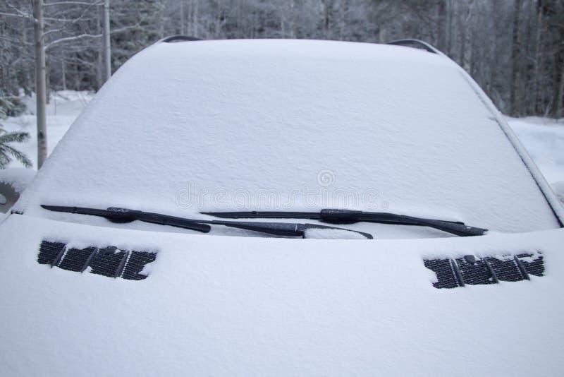 Schneebedeckter Wagen im Winterwald Die Windschutzscheibe ist schneebedeckt stockfoto