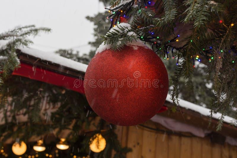 Schneefälle auf Weihnachtsmarkt mit Lichtlampen und -dekoration herein lizenzfreie stockbilder