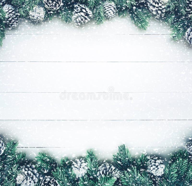 Schneefälle auf Weihnachtstannenbaum mit Kiefernniederlassungsdekoration auf weißem Holz stockfotografie