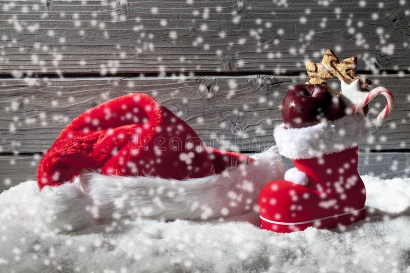 Schneefälle mit Weihnachtshut und -stiefel auf Haufen des Schnees gegen hölzernen Hintergrund stockbilder