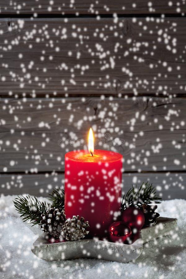 Schneefälle mit Weihnachtskerze im Kerzenhalter auf Haufen des Schnees gegen hölzernen Hintergrund stockfotografie
