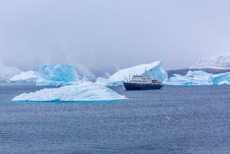 Schneefälle und Kreuzfahrtschiff unter blauen Eisbergen im Hafen Charcot, B lizenzfreies stockbild