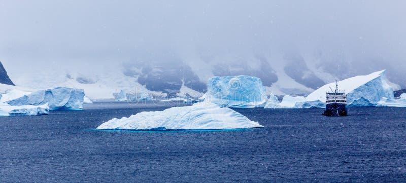 Schneefälle und Kreuzschiff unter blauen Eisbergen im Hafen Charcot, BO lizenzfreie stockfotos