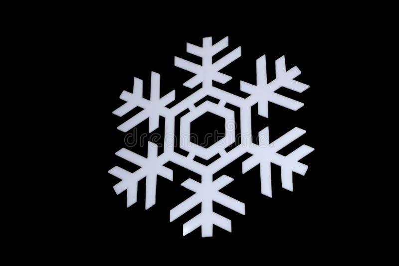 Schneeflocke lokalisiert auf schwarzem Hintergrund: Makrofoto des wirklichen Schneekristalles, gefangen genommen auf Glas mit LED stockfotografie