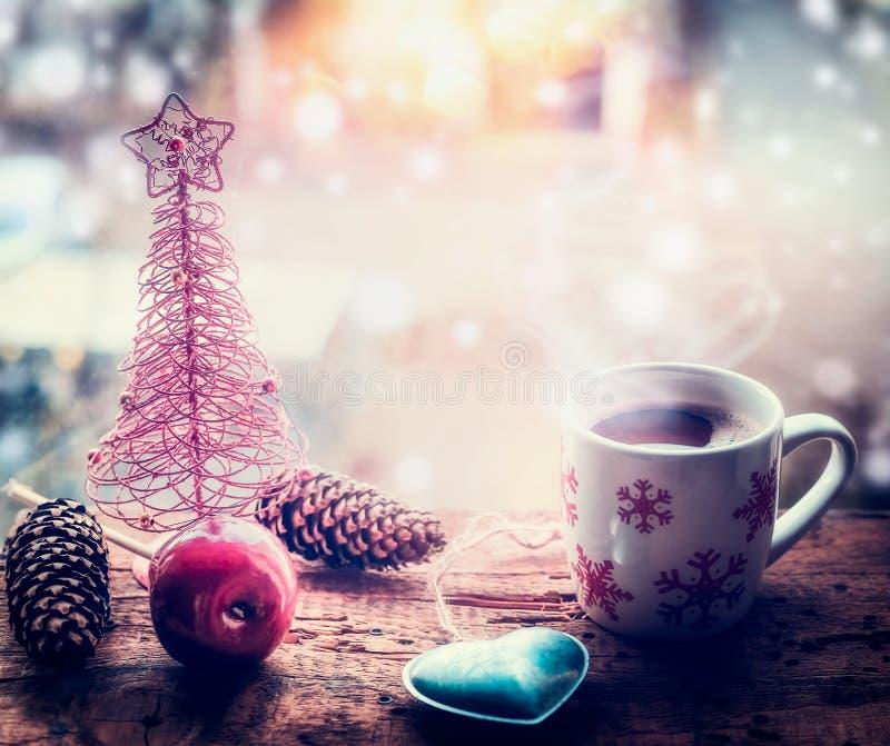 Schneeflocken überfallen mit Heißgetränk und Weihnachtsdekoration auf Fensterbrett mit Schnee lizenzfreie stockfotografie