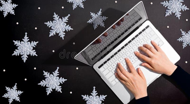 Schneeflocken mit Person, die einen Laptop benutzt stockbild