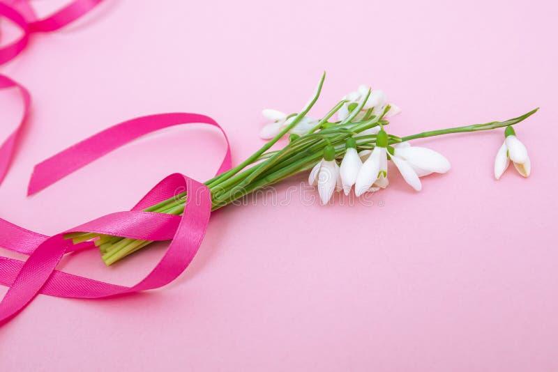 Schneeglöckchen blüht Blumenstrauß mit Band auf rosa Papierhintergrund lizenzfreie stockbilder