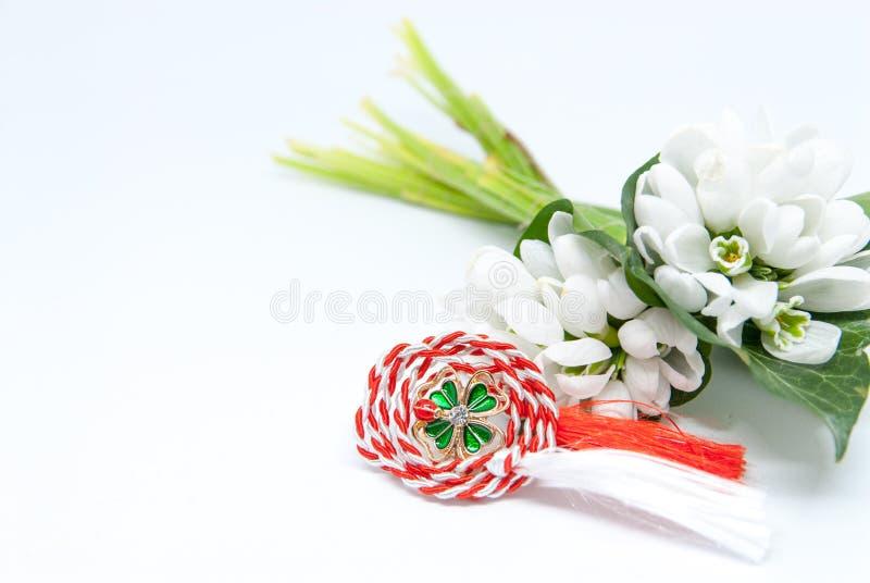Schneeglöckchen und rotes und weißes Schnur martisor auf Weiß mit dem Kopienraum osteuropäisch zuerst von der Marschtraditionsfei lizenzfreie stockfotos
