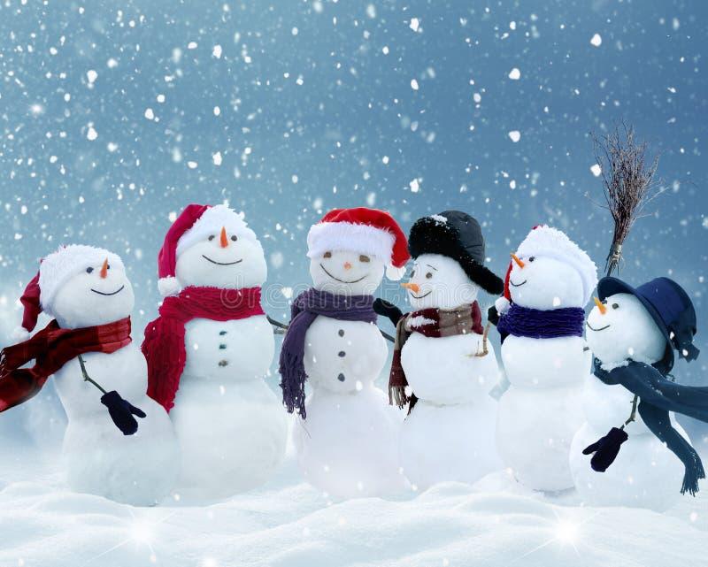 Schneemänner, die in der Winter Weihnachtslandschaft stehen lizenzfreie stockbilder