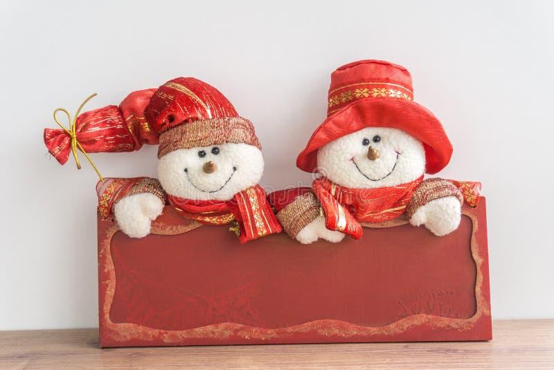 Schneemänner mit rotem Brett lizenzfreies stockbild