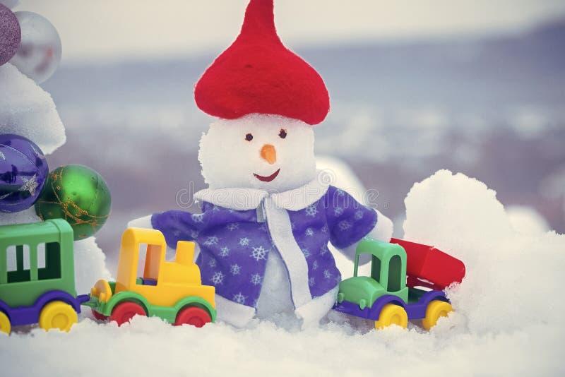 Schneemann im roten Hut und im blauen Mantel auf schneebedecktem Hintergrund stockbilder