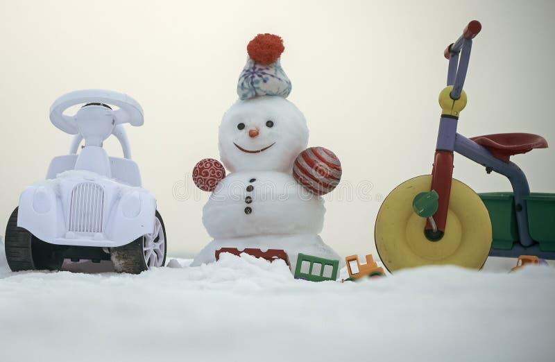 Schneemann mit smileygesicht auf weißem Himmel Dreirad, Auto und Spielwaren auf schneebedecktem Hintergrund lizenzfreies stockbild