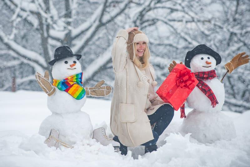 Schneemann und lustiges Mädchen im Schnee Mädchen spielen mit Snowman - isoliert auf Schneeuntergrund Joyful Beauty junge Frau lizenzfreies stockfoto