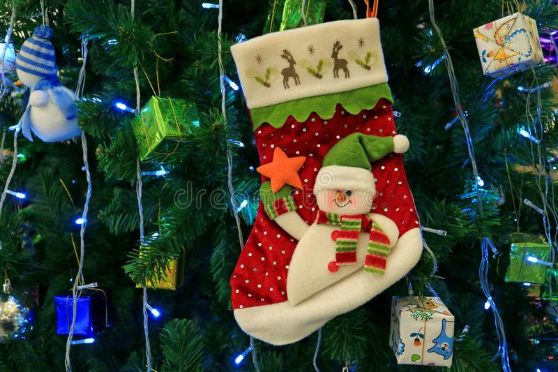 Schneemann-Weihnachtssocke mit vielen der vibrierenden farbigen Geschenkbox verziert das Hängen an einem funkelnden Weihnachtsbau stockfotografie