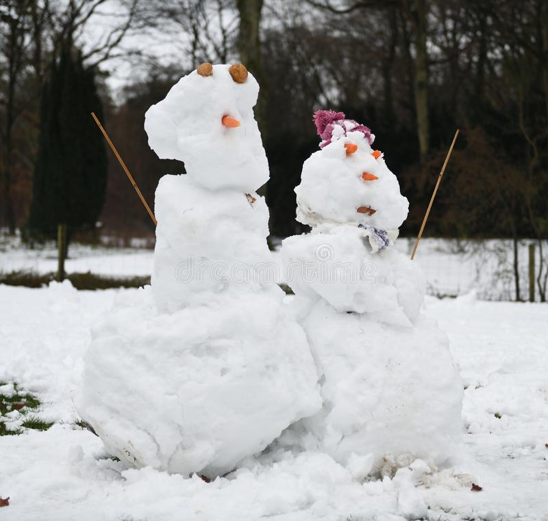Schneemannpaare im winterlichen Garten lizenzfreies stockbild