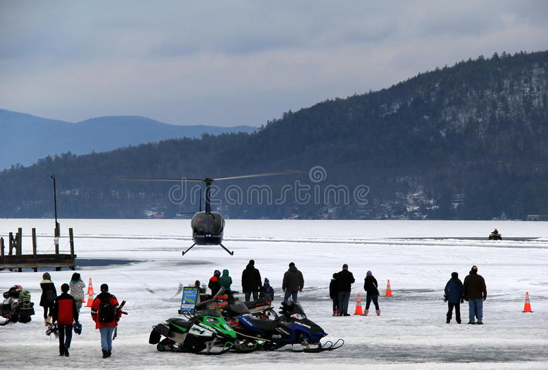 Schneemobil fahrung und Hubschrauber fährt auf See George, während Winterfest, See George New York, am 2. Februar 2014 lizenzfreies stockfoto