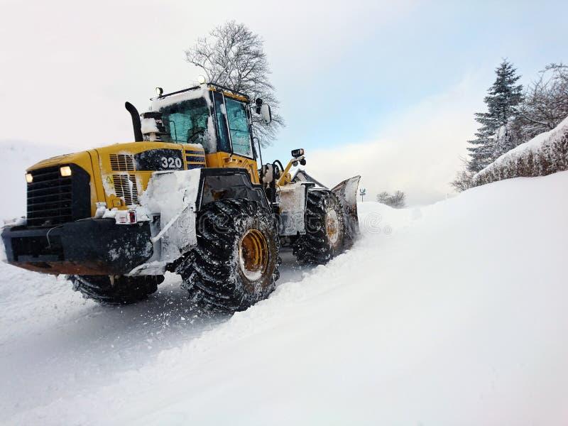 Schneeräumung mit schwerer Ladermaschinerie nach stürmischem Winter bli lizenzfreies stockfoto