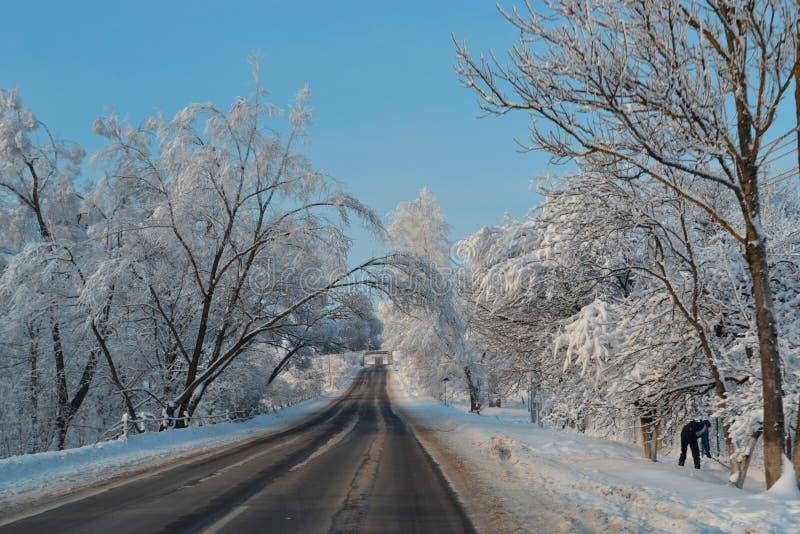 Schneestraße geht tief in magisches Märchenland des Winters Schöne Landschaft der Schneefallstraße, blauer Himmel, Weihnachtsurla stockbilder
