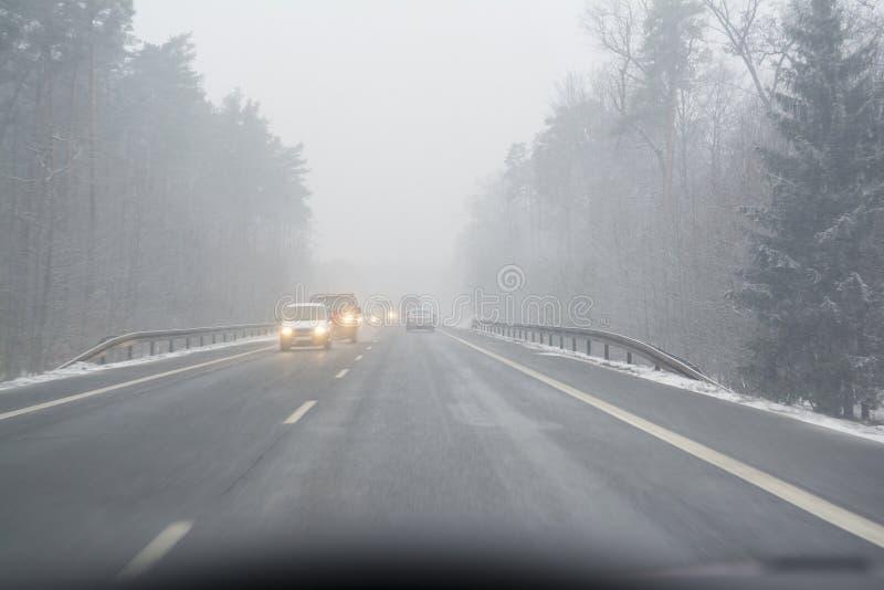 Schneesturm auf öffentlichen Straßen Erstpersonenansicht, der Fahrer des Autos auf der schneebedeckten Straße Koniferenwald auf b stockbild