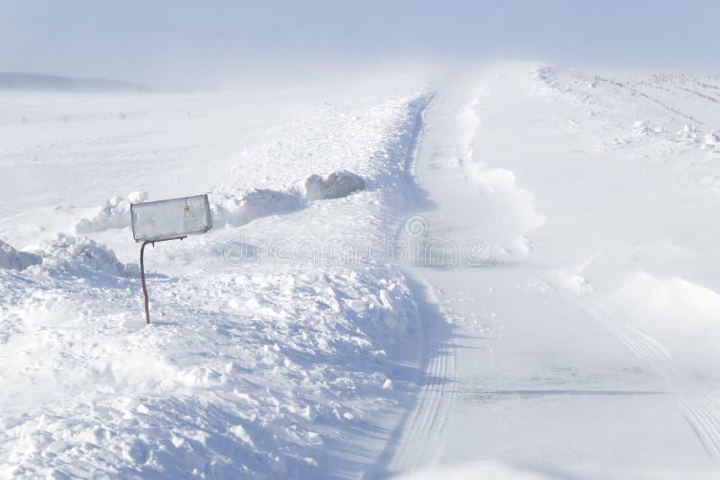 Schneeverwehungen auf einer Landstraße lizenzfreies stockfoto