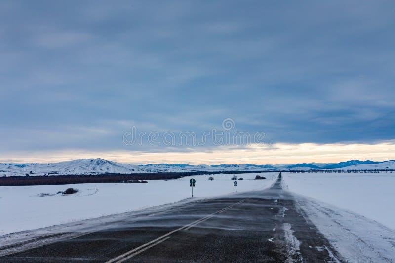 Schneeverwehungen fegen die Straße zu den Bergen in einem düsteren Himmel, Altai, Russland stockfotografie
