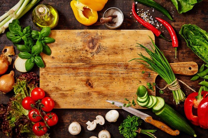 Schneidebrett und Messer mit Gemüse auf Tabelle stockbild