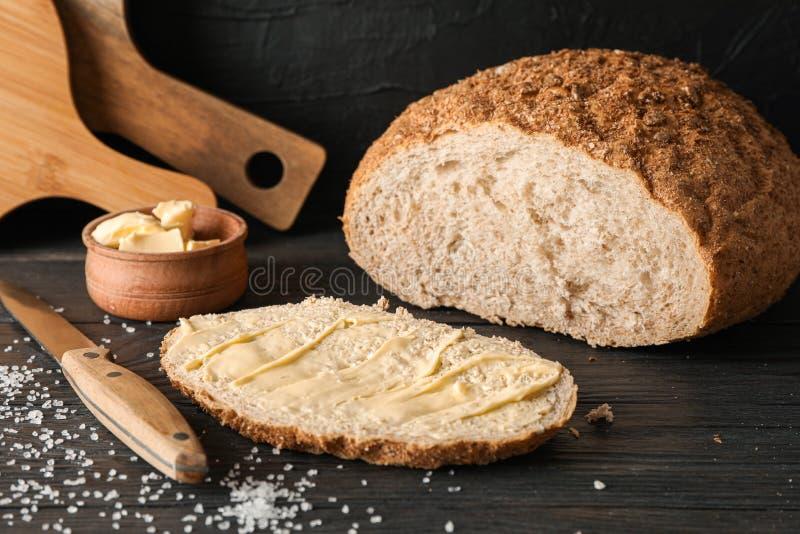 Schneidebretter, Brot, Salz, Messer und Butter auf Holztisch gegen schwarzen Hintergrund lizenzfreies stockbild