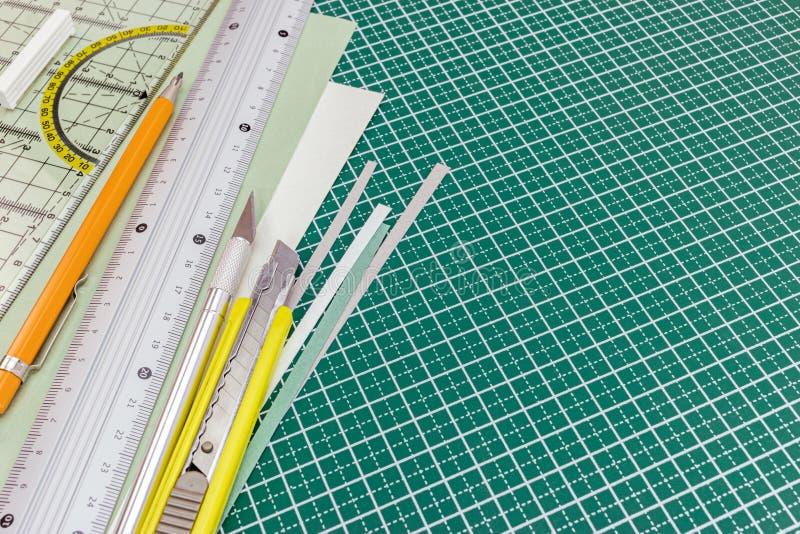 Schneidematte mit Gebrauchsmesser, mechanischer Bleistift, Metallmachthaber a lizenzfreie stockfotos