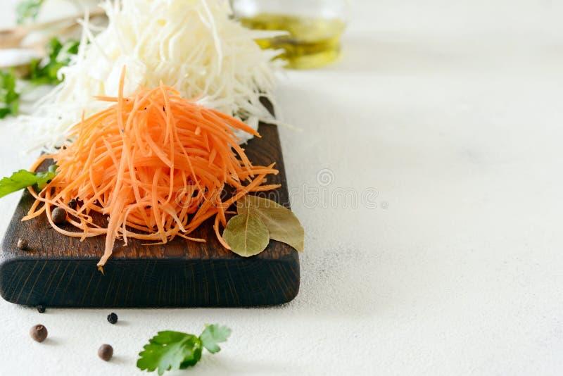 Schneiden des frischen Kohls und der Karotten auf einem hölzernen Brett auf einem hellen Hintergrund Gemüse für Ferment, für lang lizenzfreies stockfoto