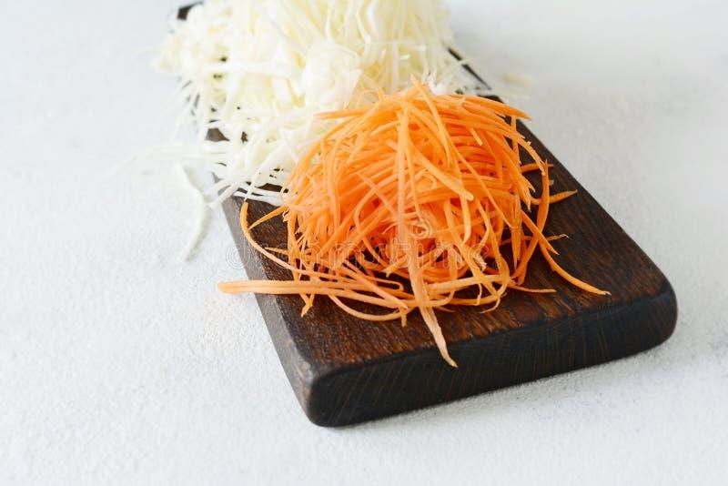 Schneiden des frischen Kohls und der Karotten auf einem hölzernen Brett auf einem hellen Hintergrund Gemüse für Ferment, für lang stockbilder