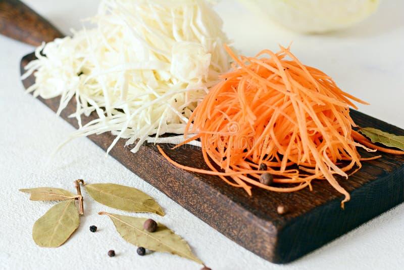 Schneiden des frischen Kohls und der Karotten auf einem hölzernen Brett auf einem hellen Hintergrund Gemüse für Ferment, für lang lizenzfreie stockbilder