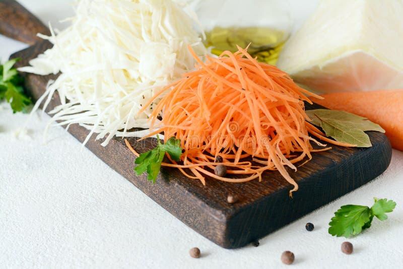 Schneiden des frischen Kohls und der Karotten auf einem hölzernen Brett auf einem hellen Hintergrund Gemüse für Ferment, für lang lizenzfreie stockfotos