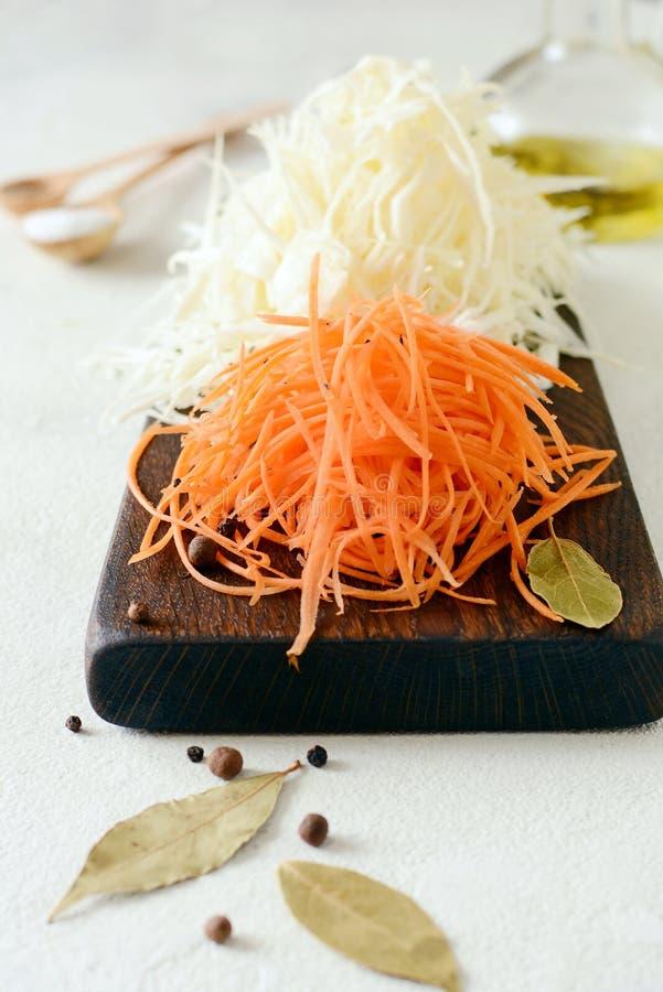 Schneiden des frischen Kohls und der Karotten auf einem hölzernen Brett auf einem hellen Hintergrund Gemüse für Ferment, für lang stockfotos