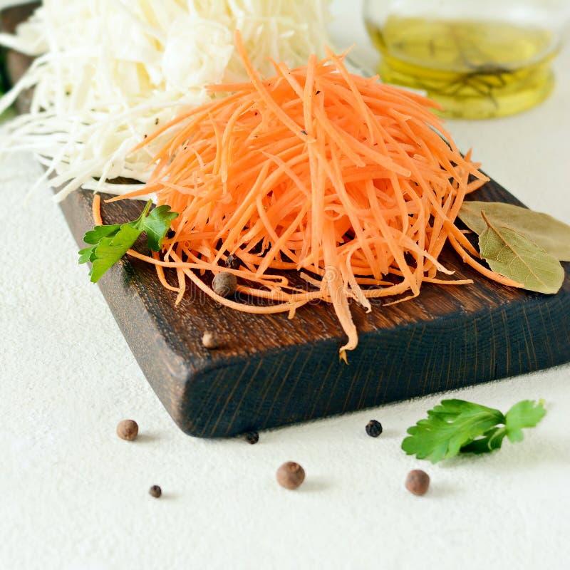 Schneiden des frischen Kohls und der Karotten auf einem hölzernen Brett auf einem hellen Hintergrund Gemüse für Ferment, für lang lizenzfreie stockfotografie