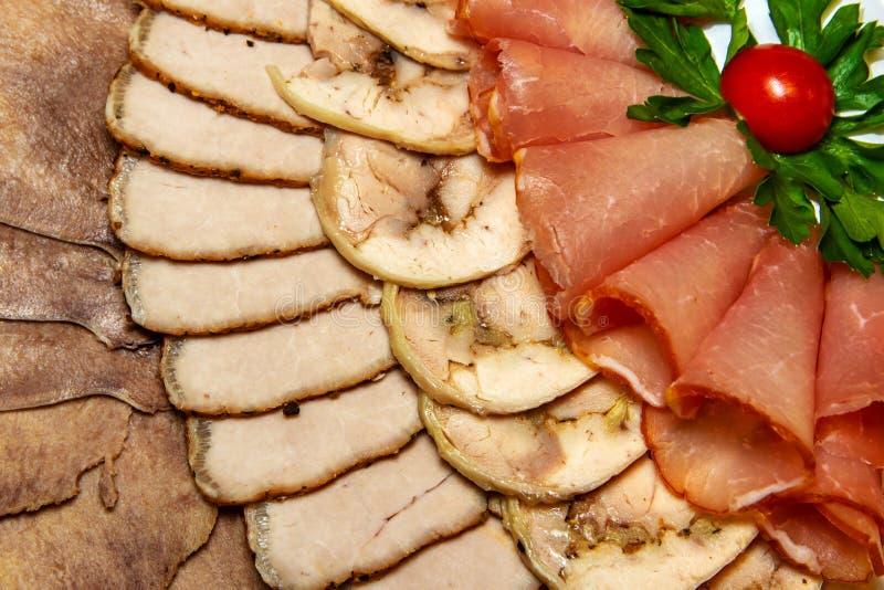 Schneiden des unterschiedlichen Fleisches in einer Platte mit Tomate und grünen Blättern auf Platte stockfoto