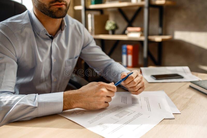 Schneiden Sie Ansicht des jungen hübschen Geschäftsmannes in seinem eigenen Büro Er hält Stift in den Händen Dokumente auf Tabell stockbild
