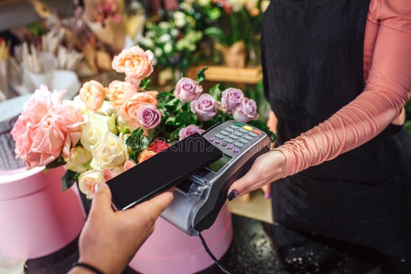 Schneiden Sie Ansicht des Mannholdingtelefons über Geld therminal Viele Blumen und Anlagen sind hinter lizenzfreie stockfotos
