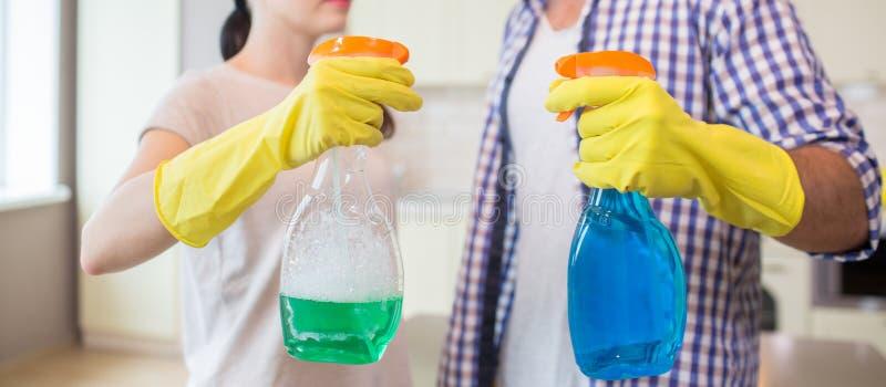 Schneiden Sie Ansicht von zwei kastrieren Flaschen Sie werden vom Mann und von der Frau gehalten Mädchen hält grüne Sprühflasche, stockbild