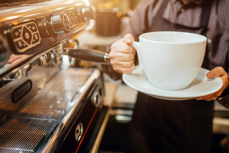 Schneiden Sie die Ansicht von barista enormen weißen Tasse Kaffee in den Händen halten Er steht in der Küche an der Kaffeemaschin stockbild