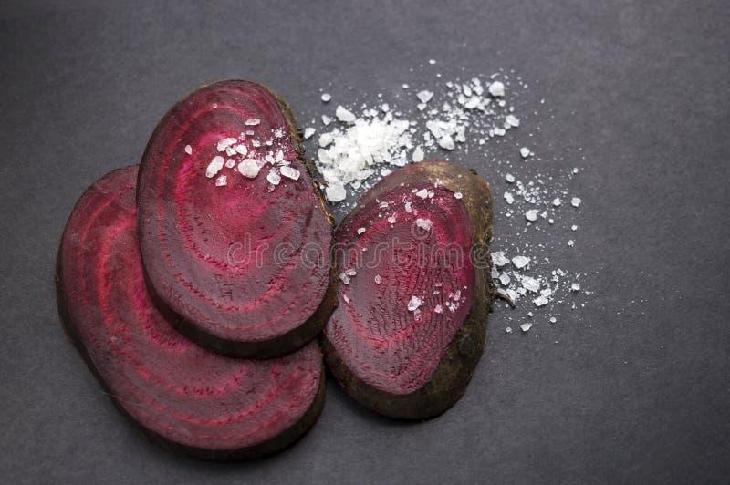 Schneiden Sie frische Rote-Bete-Wurzeln und Salz auf der schwarzen Oberfläche stockfotos