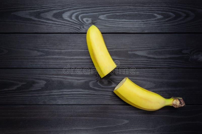 Schneiden Sie in halbe Banane auf dunklem hölzernem Hintergrund stockfoto