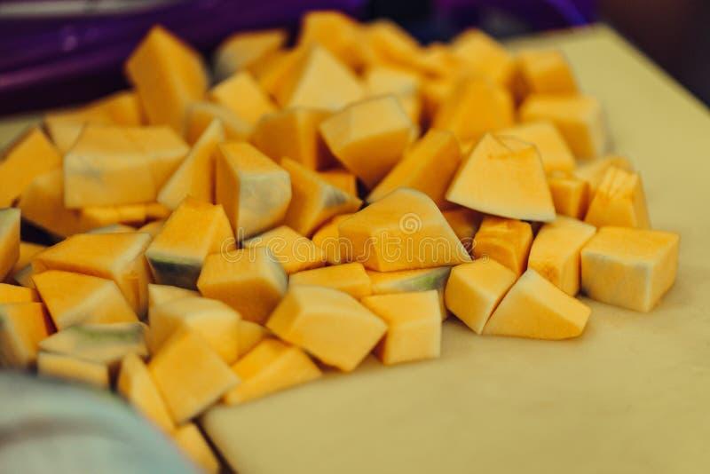Schneiden Sie Kürbis-Stücke auf dem gelben Plastikbrett lizenzfreies stockfoto