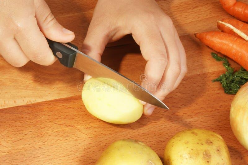 Schneiden Sie Kartoffel, um Gemüsesuppe zu bilden lizenzfreie stockfotografie