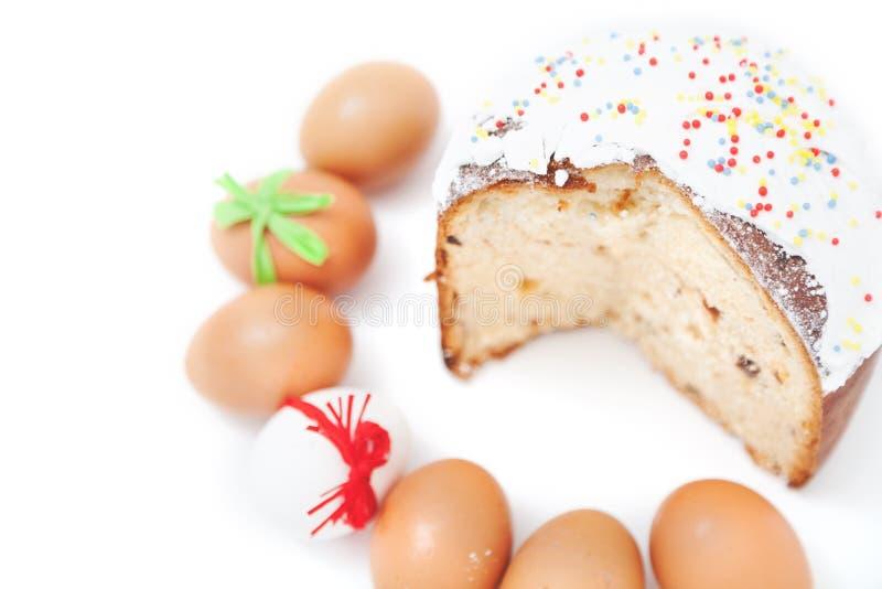 Schneiden Sie Kuchen und Zahl von Ostereiern auf weißem Hintergrund lizenzfreie stockbilder