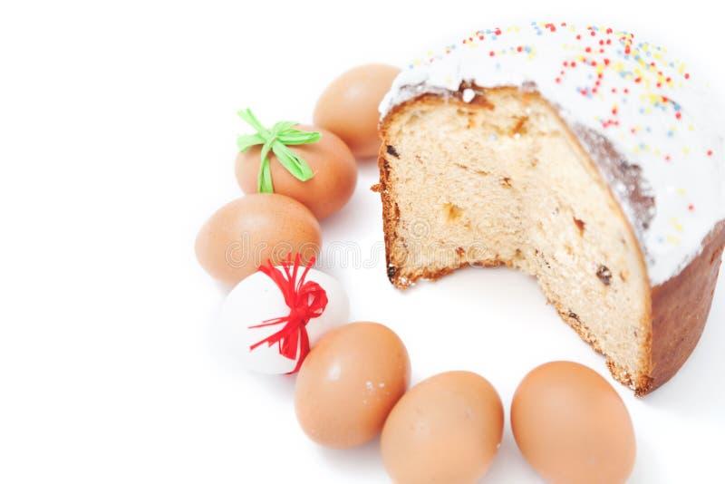Schneiden Sie Kuchen und Zahl von Ostereiern auf weißem Hintergrund lizenzfreie stockfotografie