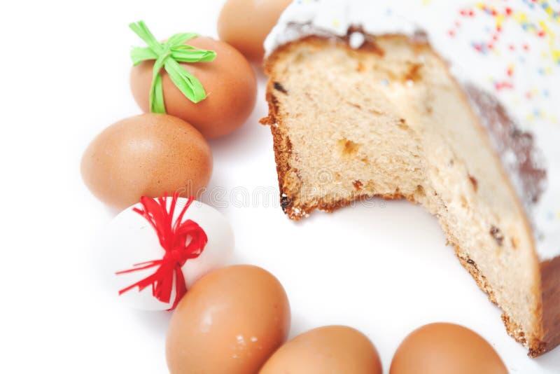 Schneiden Sie Kuchen und Zahl von Ostereiern auf weißem Hintergrund stockfotos