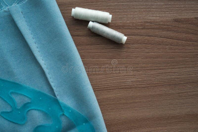 Schneiden Sie Rock im blauen Gewebe, im Plastikstück und in zwei Spulen grauem Faden auf einer tailor's braunen Tabelle Copyspa lizenzfreie stockfotografie